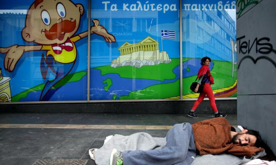 A homeless person sleeps under an image of Parthenon with the Greek flag in Athens.
