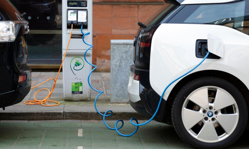 Two electric cars charging on a street of Glasgow.