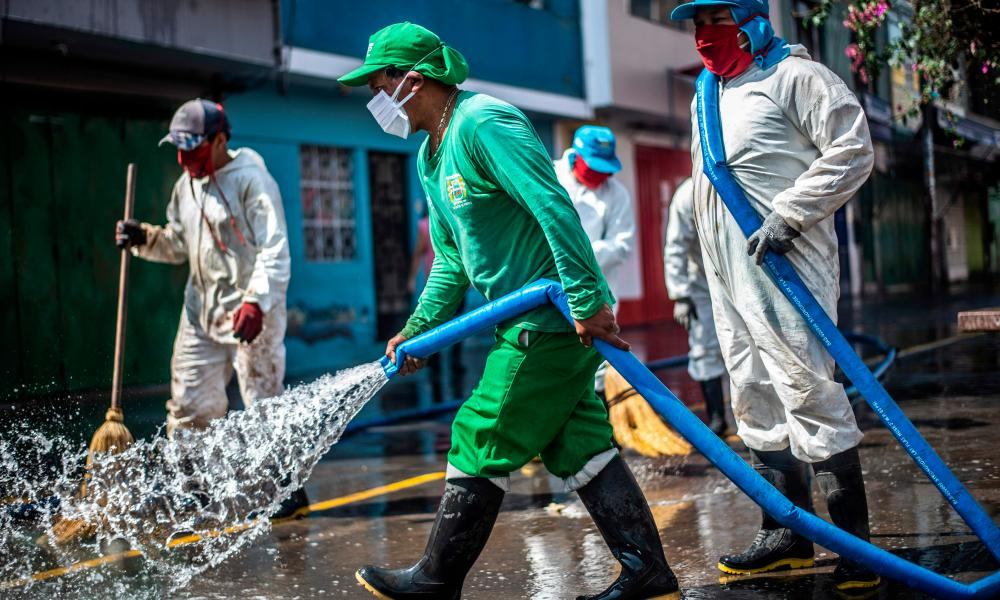 Municipal workers clean and disinfect the surroundings of the Caqueta market in the north of Lima on 30 April 2020.