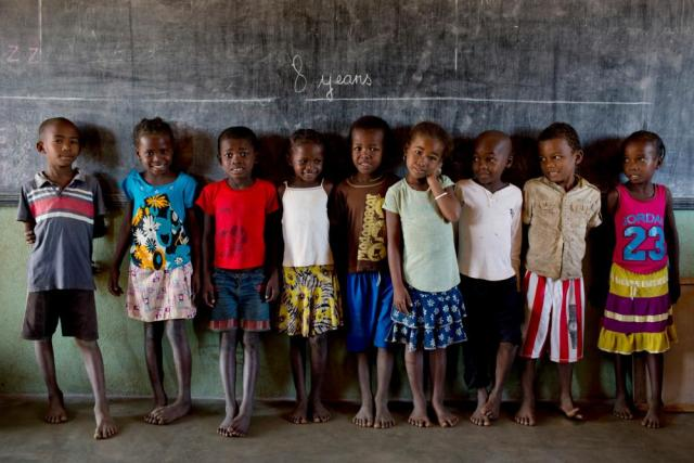 Children at a primary school in Madagascar's Bemanonga commune stand beneath a chalk line indicating how tall children of eight years old should be.
