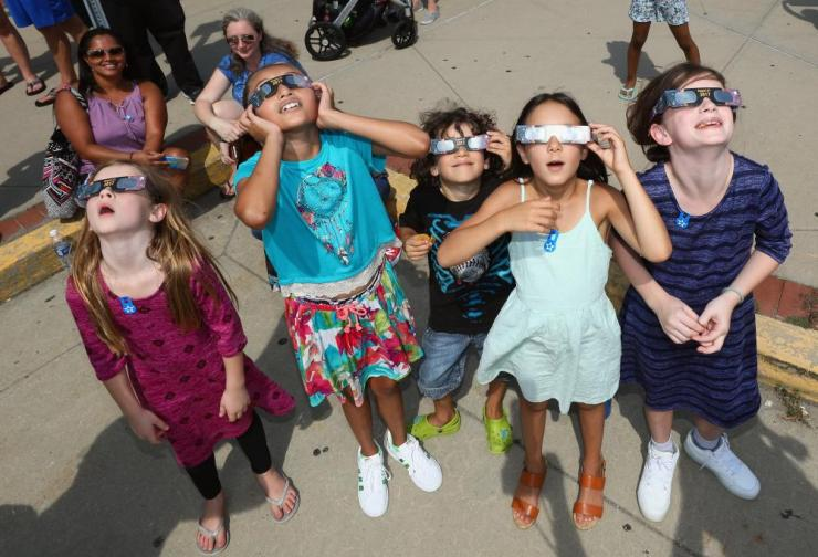 Spectators look skyward during a partial eclipse of the sun at the Cradle of Aviation Museum in Garden City, New York.