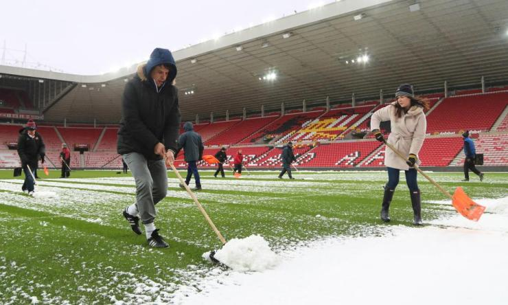 Manager Chris Coleman helps as Sunderland staff clear the pitch to enable first team training at Stadium of Light on Thursday