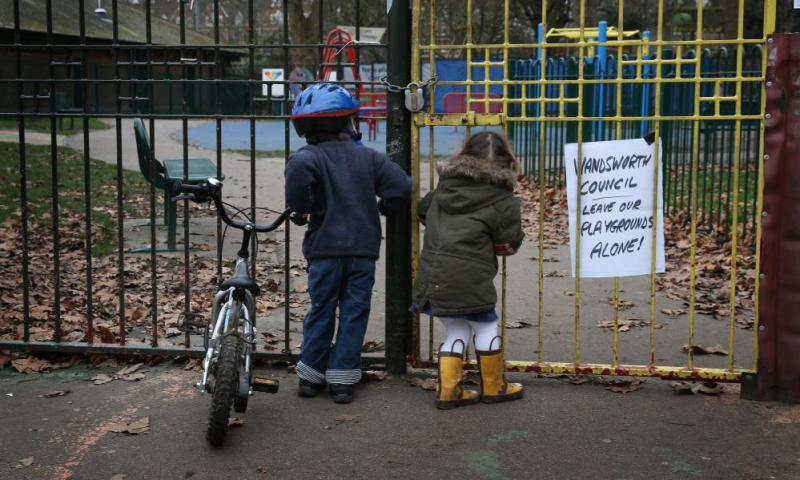 Children look into a closed playground next to Battersea Park, London.