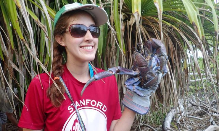 A Stanford researcher holds a crab at Bikini Atoll.