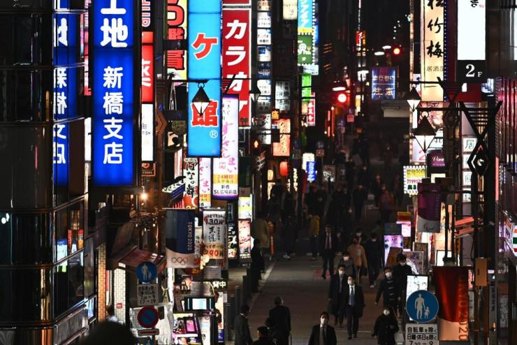 People walk through the Shinbashi nightclub district in Tokyo in March.