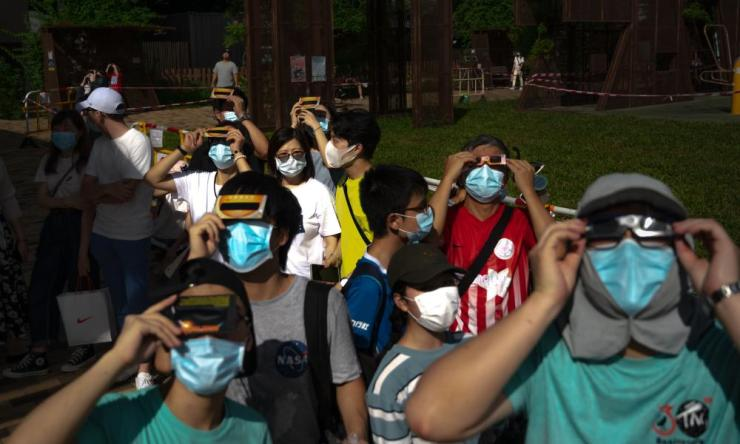 People wear face masks to help curb the spread of  coronavirus as they observe the partial solar eclipse at Olympic park on June 21, 2020 in Beijing, China.