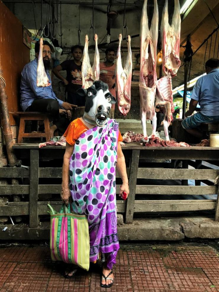 A woman in a cow mask at a butcher's shop