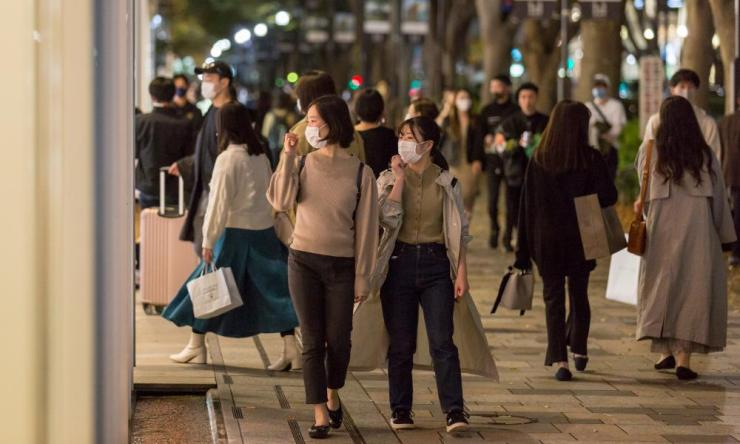 Shoppers wearing face masks walk in the Omotesando area of Tokyo, Japan.