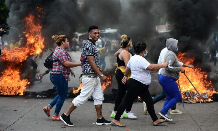 People walk near a burning barricade set up by street vendors during a protest to demand the government of Honduran President Juan Orlando Hernandez to allow them to work at the Belen market amid the economic crisis triggered by the coronavirus pandemic, in Tegucigalpa. Over 2,500 people died in Honduras due to the new coronavirus out of at least 86,100 contagions.