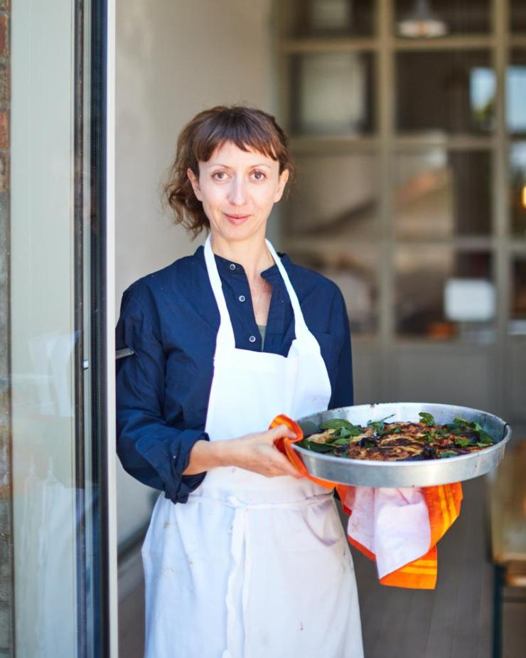 Marianna Leivaditaki, chef of Morito, standing in a doorway holding a metal dish