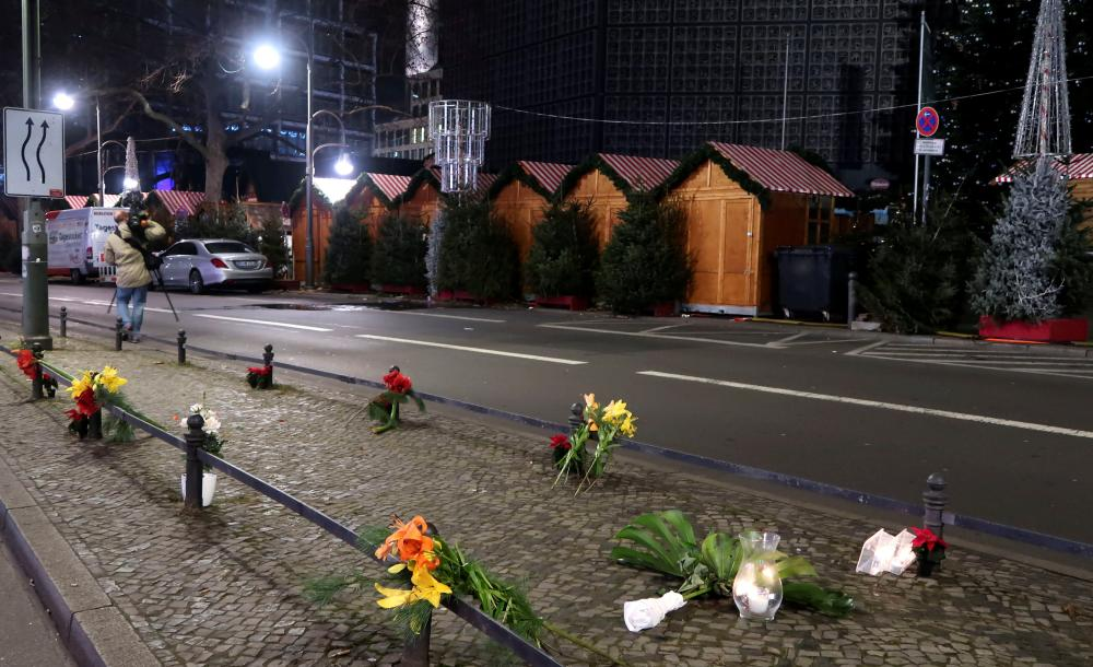 Candles and flowers near the site where a truck ploughed through a crowd at a Berlin Christmas market.