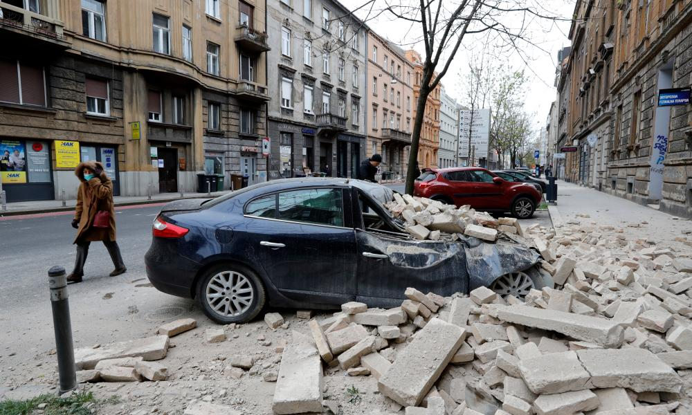 A person walks past rubbles lying on a street after a 5.3-magnitude earthquake that hit near Zagreb, Croatia