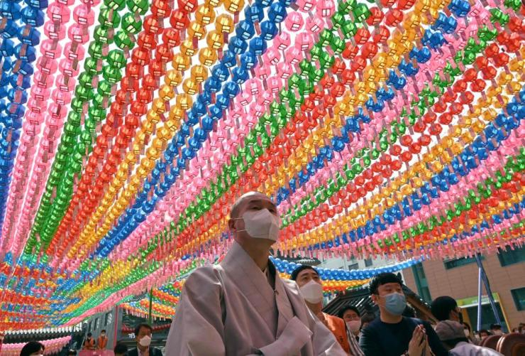 A Buddhist monk under rows of lotus lanterns at the birthday celebration at Jogye temple.