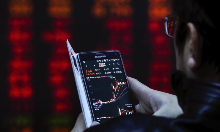 An investor checks stock prices through his smartphone at a brokerage house in Beijing