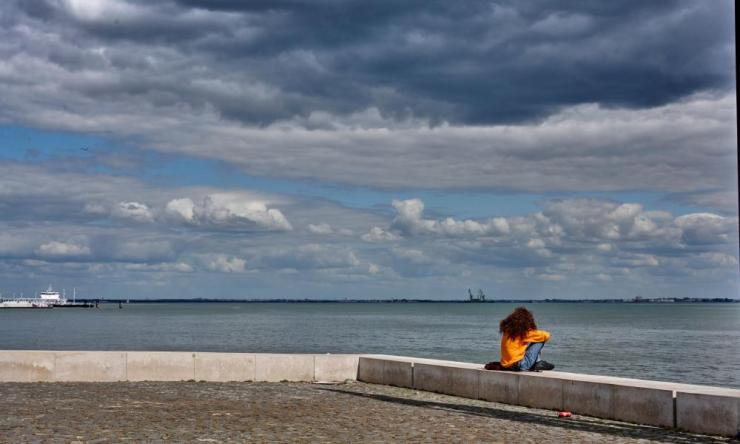 A woman sits facing the Tagus River in Ribeira das Naus a day before the end of the state of emergency during the pandemic on April 29, 2021 in Lisbon, Portugal.