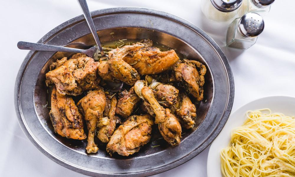 Dish of chicken legs and thighs in a metal dish, next to a bowl of spaghetti, from Mosca's, New Orleans, US.