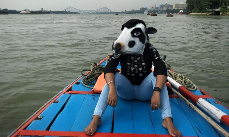 A woman in a cow mask sits on a boat