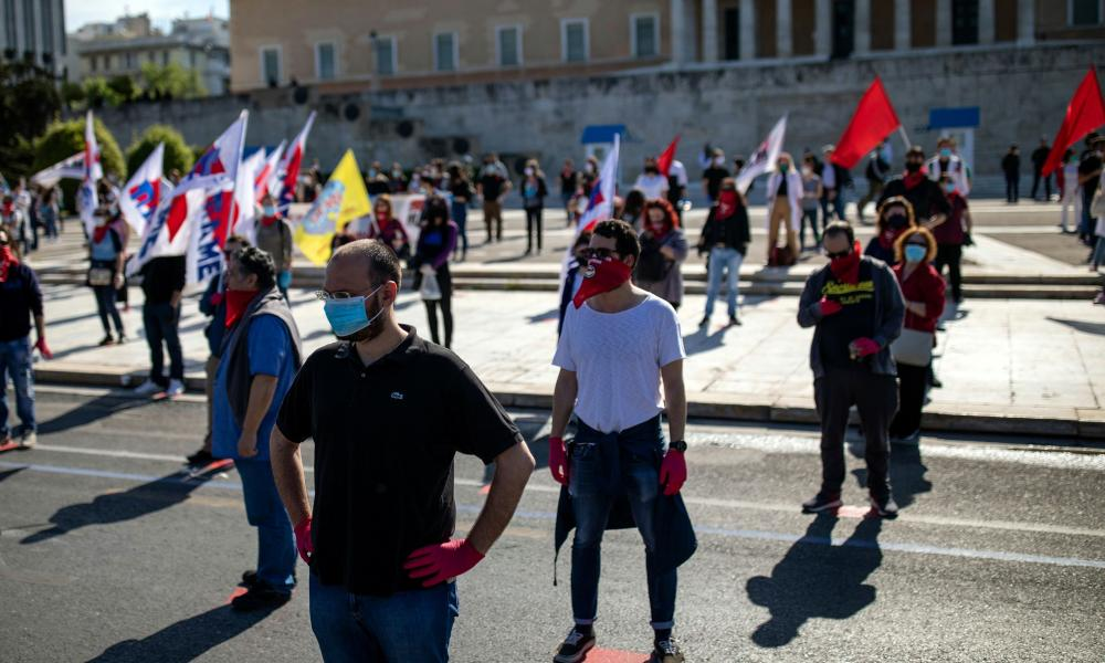 Members of the communist-affiliated trade union PAME wearing protective masks and gloves practise social distancing during a rally commemorating May Day in Athens