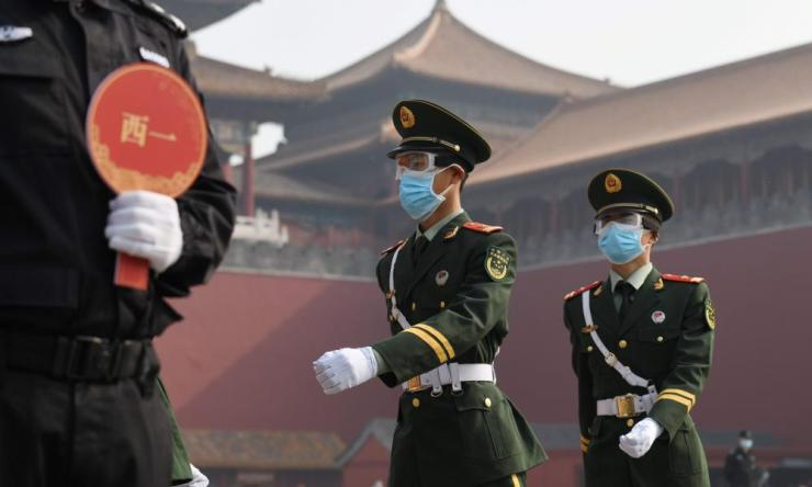 Paramilitary police officers wear face masks and goggles as they march outside the Forbidden City, the former palace of China's emperors, in Beijing on 1 May 2020.