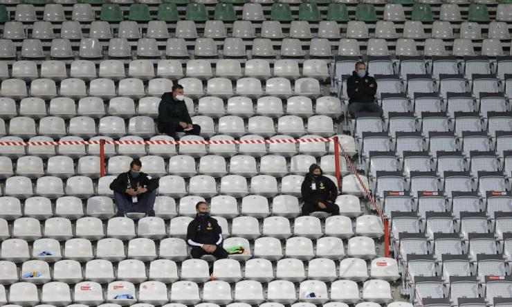 Team staff wear face masks sit in the stands during the German first division Bundesliga football match between SC Freiburg and Borussia Moenchengladbach.