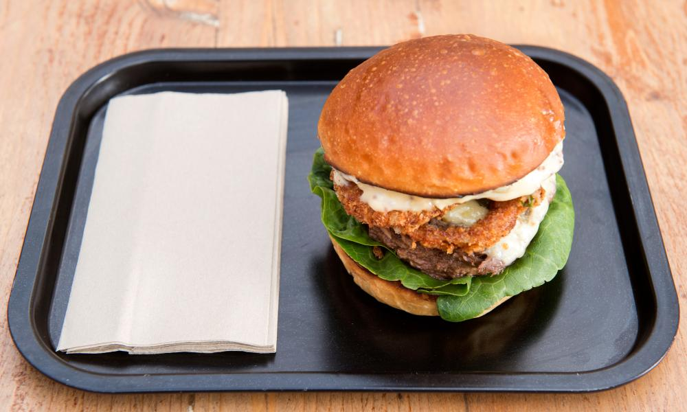 The tall Hereford Hop burger, on a plain tray with a serviette
