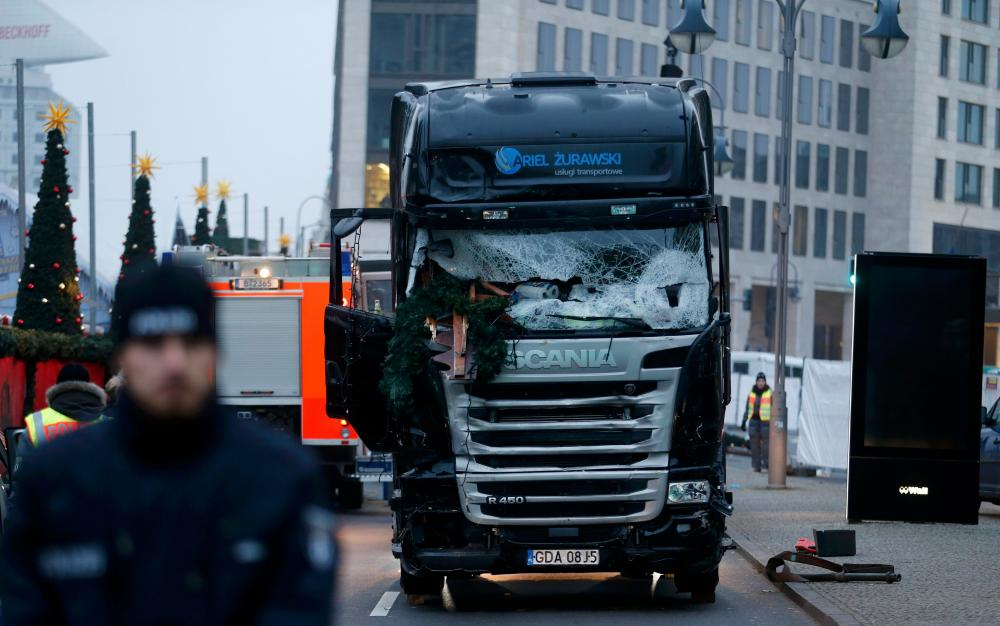 Police stand in front of the truck that ploughed into a crowded Christmas market in the German capital on Monday night.