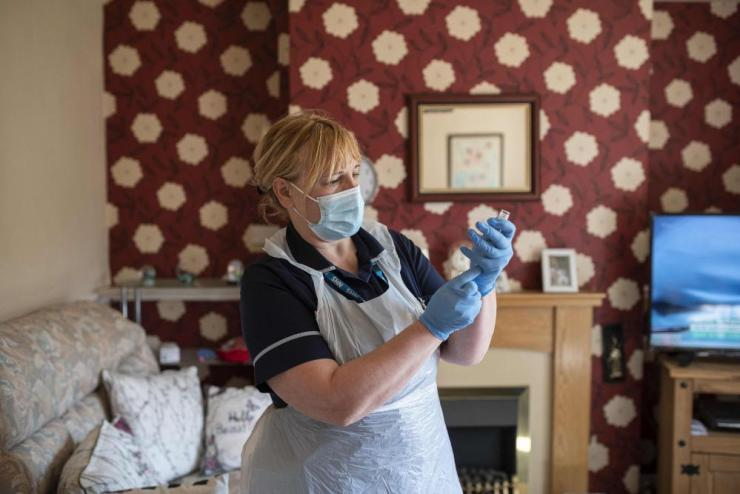 Team leader for housebound vaccinations, Julie Fletcher, prepares to administer a dose of the AstraZeneca/Oxford Covid-19 vaccine to housebound patient Gillian Marriott at her home in Hasland, near Chesterfield, central England on 14 April, 2021.