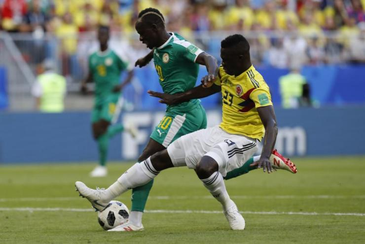 Colombia's Davinson Sanchez challenges for the ball and clearly hooks it away with his heel.