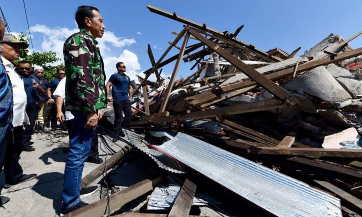 Indonesian President Joko Widodo looks at the damage following earthquakes and a tsunami in Palu)