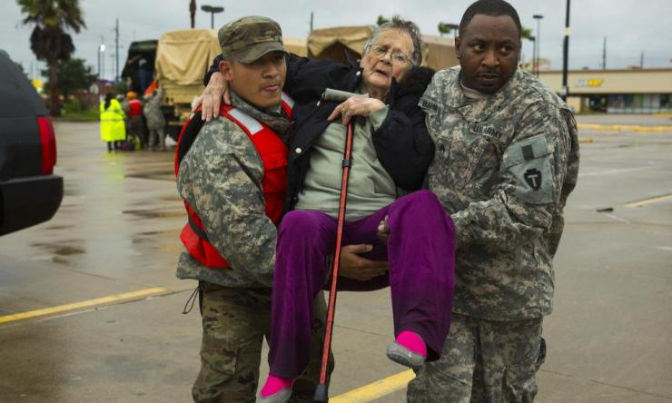 Texas Army National Guard members Sergio Esquivel, left, and Ernest Barmore carry 81-year-old Ramona Bennett after she and other residents were rescued from their Pine Forest Village neighborhood due to high water from Hurricane Harvey.
