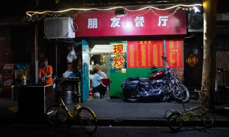 A Harley-Davidson motorcycle parked in front of a restaurant in Shanghai.