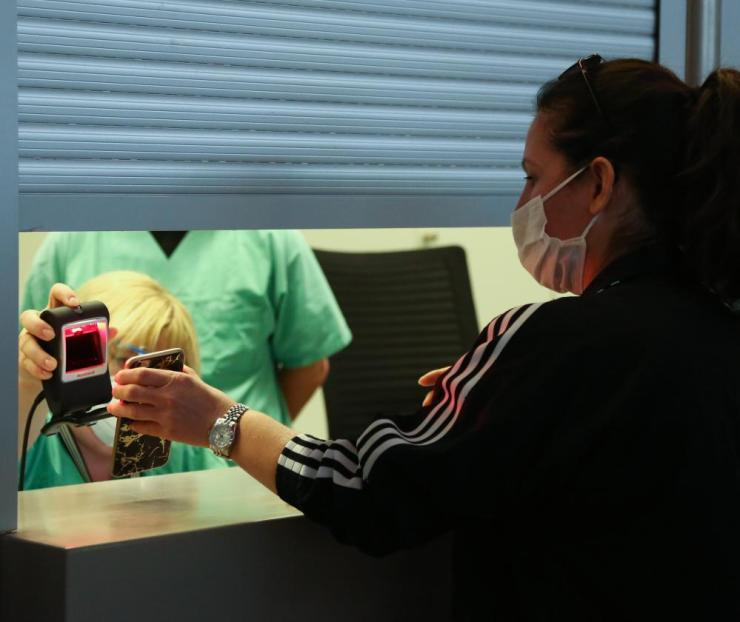 A newly-arrived passenger uses a mobile phone to register to be tested for coronavirus at Tegel (TXL) airport in Berlin, Germany.