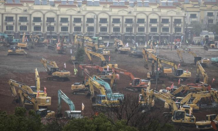 Workers driving excavators at the construction site of the 1,000-bed hospital that is to be built by February 3 to cope with the surge of 2019-nCoV patients in the city