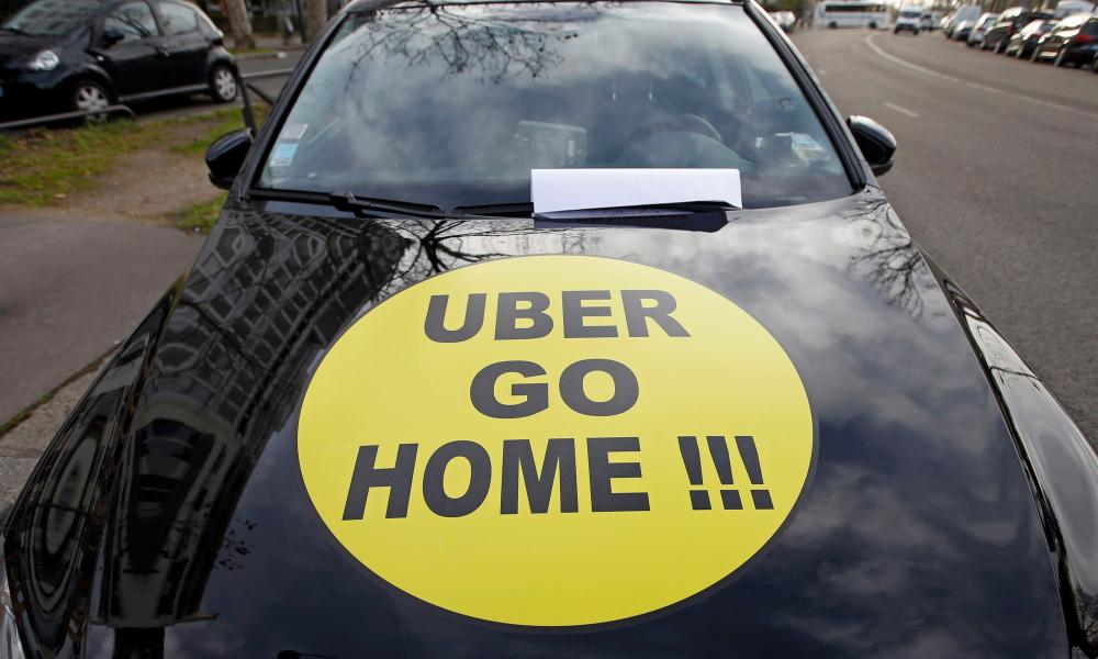 "A striking French taxi drivers displays the message, ""Uber Go Home"" during a national protest"