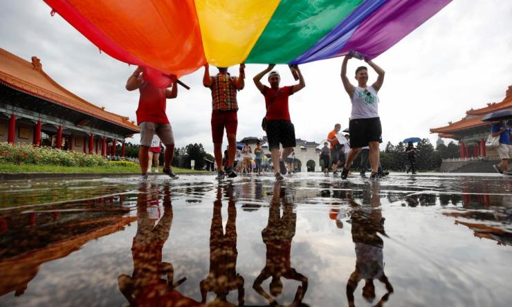 Members of the LGBT community hoist a rainbow flag as they march to celebrate the Pride month at the National Chiang Kai-shek Memorial Hall in Taipei, Taiwan, 28 June 2020. Due to the coronavirus pandemic, Taiwan is one of the few countries to hold this year's 50th anniversary Pride March. Credit: EPA/RITCHIE B. TONGO