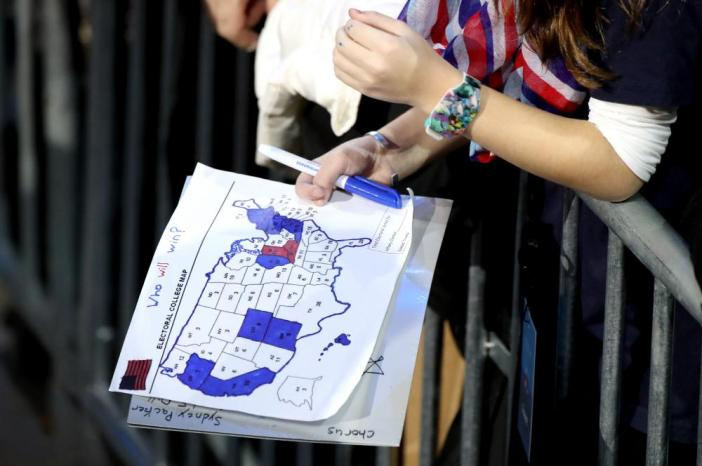 A woman holds a homespun electoral map but her count doesn't show many signs of the wins by Trump throughout the central and southern states, including Florida.