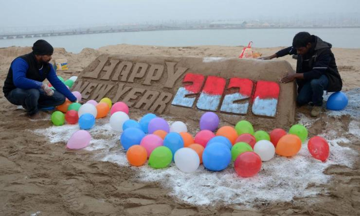 Students of Allahabad Central university make a sand sculpture on the eve of New Year Celebration in Allahabad.