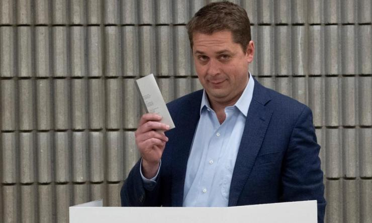 Conservative leader Andrew Scheer holds up his ballot after marking his choice at a polling station in Regina, Saskatchewan.