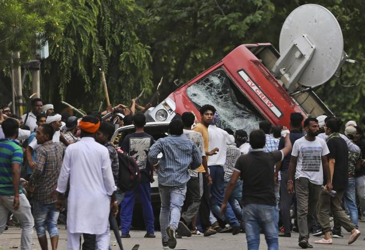 Sect members overturn an outside broadcast van in Panchkula during deadly riots.