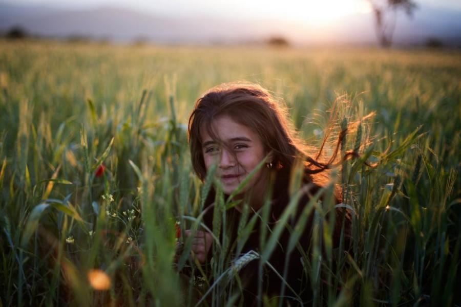 Milaf, seven, picks flowers in the fields along the Macedonian border.