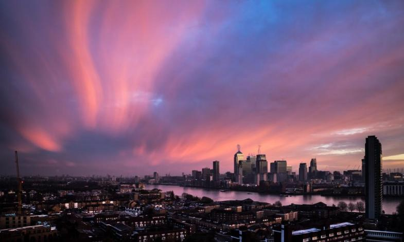 Dramatic and colourful morning sunrise over Canary Wharf in London<br>23 Nov 2015, London, England, UK --- London, United Kingdom. 23rd November 2015 -- Cold wintery air brings dramatic light and pinky/orange colours to a morning sunrise over Canary Wharf business park buildings and River Thames in central London, UK. -- The cold wintery air brings dramatic light and pinky/orange colours to a morning sunrise over Canary Wharf business park buildings in central London, UK. --- Image by © Guy Corbishley/Demotix/Corbis