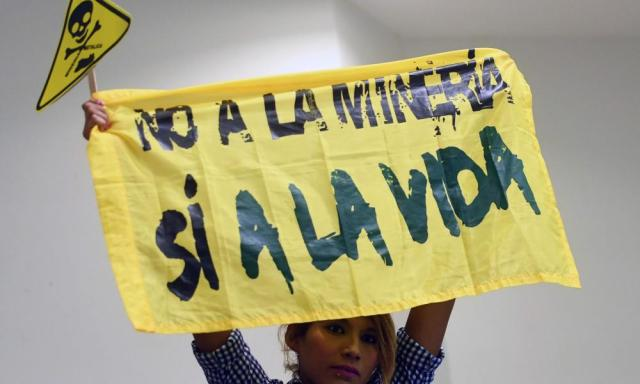 At a protest against mining at the legislative assembly in San Salvador, a woman holds a banner reading: 'No to mining. Yes to life.'