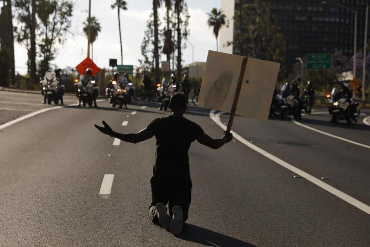 "A man kneels on the street in front of police officers while chanting ""I can't breathe"" during a protest over the death of George Floyd, Friday, May 29, 2020, in Los Angeles. Floyd died Memorial Day while in police custody in Minneapolis. (AP Photo/Jae C. Hong)"