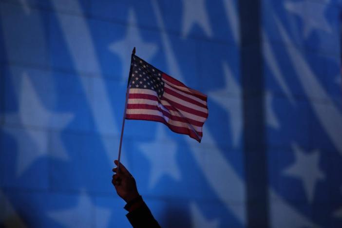 Howard Nizebeth waves a U.S. flag during an Election Day gathering at Rockefeller Center.