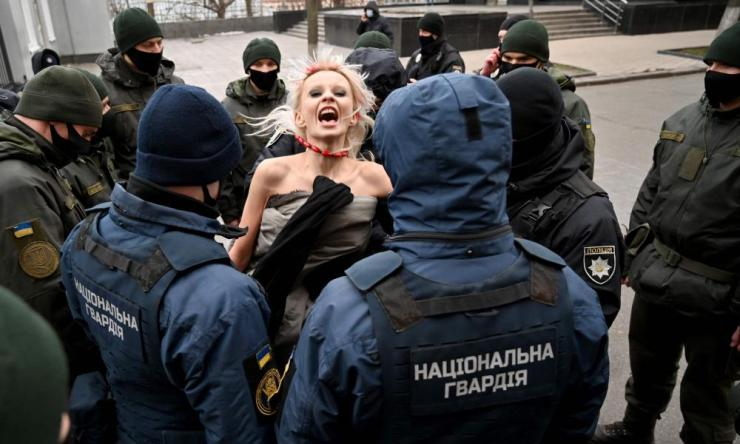 Police officers arrest an activist of Femen movement protesting outside Ukrainian President's to mark the International Day for the Elimination of Violence against Women in Kiev on 25 November 2020.
