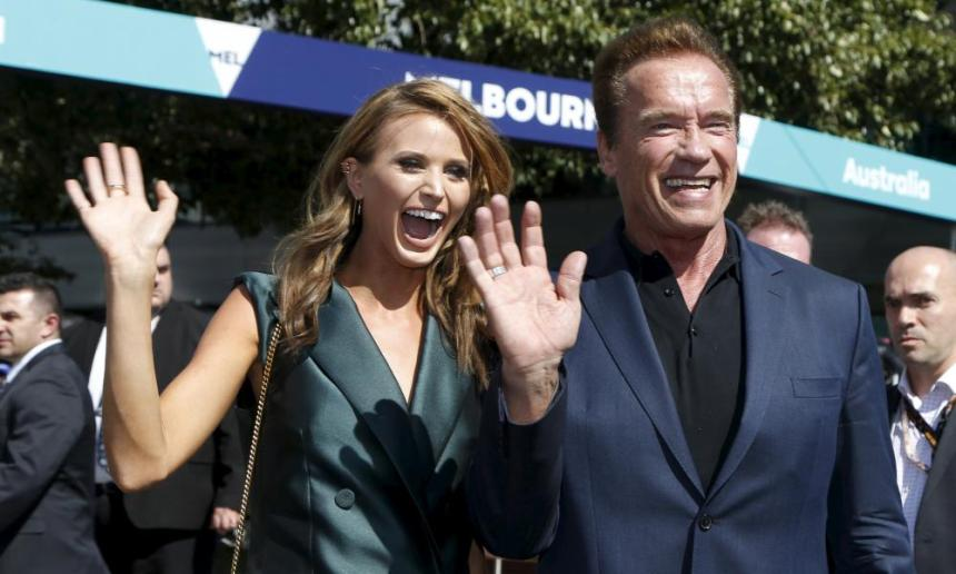 Arnold Schwarzenegger and F1 ambassador Britney Davis arrive at the Australian Formula One Grand Prix in Melbourne.