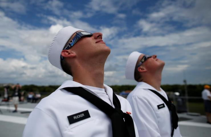 U.S. Navy sailors Soloman Rucker (Front) and Peyton Warner check the position of the sun on the flight deck of the Naval museum ship U.S.S. Yorktown during the Great American Eclipse in Mount Pleasant, South Carolina.
