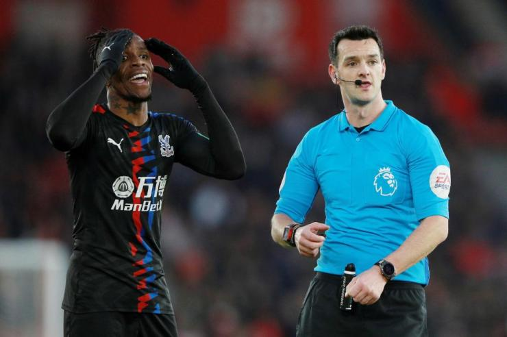 Crystal Palace's Wilfried Zaha reacts next to referee Andrew Madley.