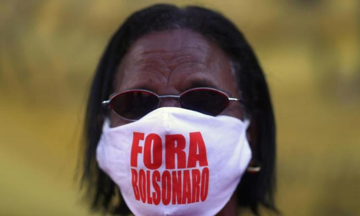 "A demonstrator wears a mask reading ""Bolsonaro out"" during a protest against Brazil's president Jair Bolsonaro in Rio de Janeiro, Brazil on 13 June, 2020. Photo: REUTERS/Pilar Olivares"