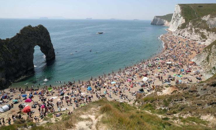 People enjoying the good weather on the beach at Durdle Door, near Lulworth in Dorset, as the public are being reminded to practice social distancing following the relaxation of lockdown restrictions on Saturday, 30 May, 2020. Photo credit: Andrew Matthews/PA Wire